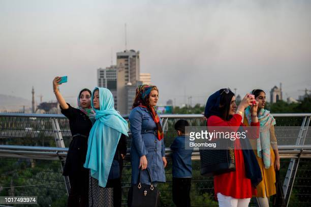 Pedestrians pause to take photographs as they promenade along the Tabiat bridge in Tehran Iran on Saturday Aug 4 2018 Irans central bank acting on...