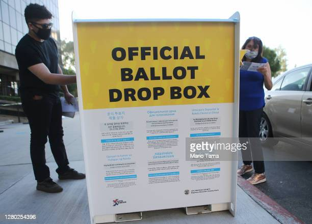 Pedestrians place ballots in an official mailin ballot drop box outside of the LA County Registrar's office ahead of Election Day on October 14 2020...