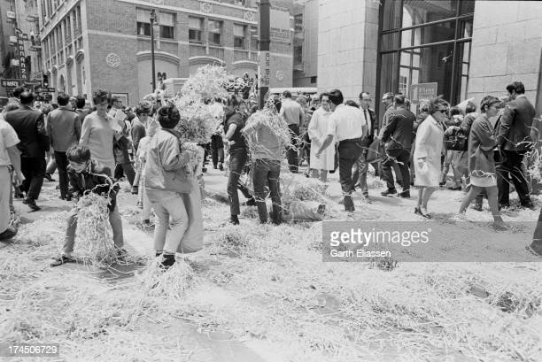 Pedestrians play with piles of ticker tape left behind after a parade in honor of the Apollo 10 astronauts on Montgomery Street San Francisco...