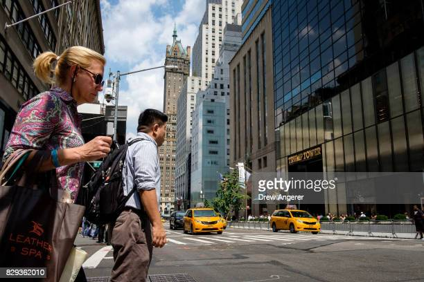 Pedestrians prepare to cross Fifth Avenue across the street from Trump Tower August 10 2017 in New York City Scheduled to arrive Sunday evening and...