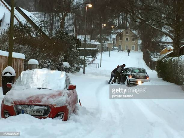 Pedestrians pushing a snowedin car on Thursday morning in Flensburg Germany 01 March 2018 Snowbanks up to a metre high resulted in roads in Flensburg...
