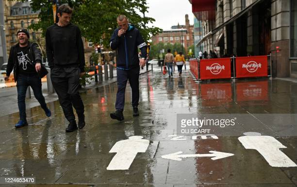 Pedestrians react as they walk past raincovered signs painted onto the pavement reminding people to maintain two metres apart and social distance as...