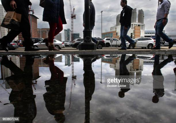 Pedestrians reflected in a puddle on Boston Wharf Road pass in front of the parking lot that will be the future site of a new Amazon building...