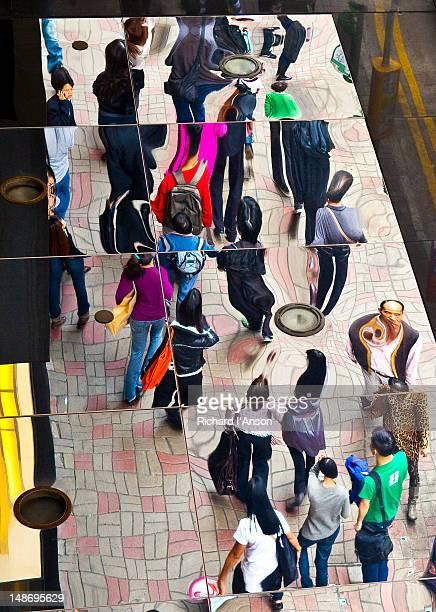 Pedestrians reflected in mirror, Central.