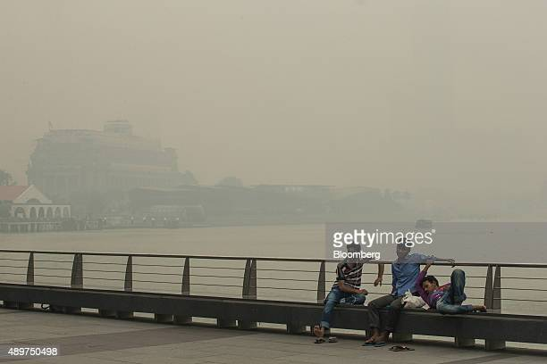 Pedestrians rest in the Marina Bay district as The Fullerton hotel stands shrouded in smog in Singapore, on Thursday, Sept. 24, 2015. The haze from...