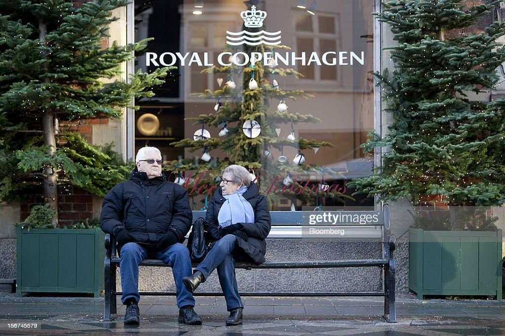 Pedestrians rest on a bench on a shopping street outside a Royal Copenhagen A/S store in central Copenhagen, Denmark, on Monday, Nov. 19, 2012. Denmark's two-year yields sank to the lowest in almost three months in Copenhagen trading as Europe's debt crisis continues to drive investors north. Photographer: Linus Hook/Bloomberg via Getty Images