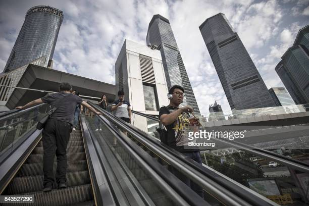 Pedestrians ride an escalator in the Lujiazui Financial District in Shanghai China on Monday Sept 4 2017 The Chinese central bank's tight leash on...