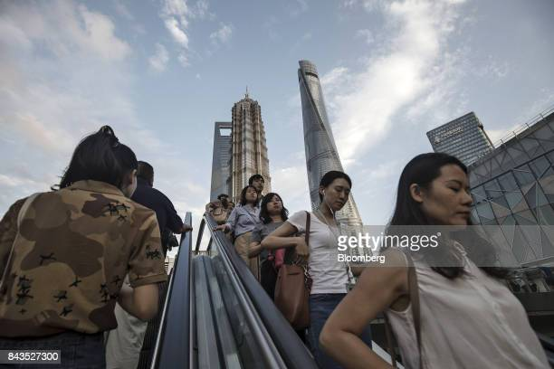 Pedestrians ride an escalator near the Jin Mao Tower center left and the Shanghai Tower center right in the Lujiazui Financial District in Shanghai...