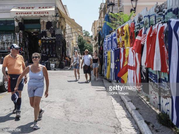 Pedestrians seen walking past Greek and foreign flags