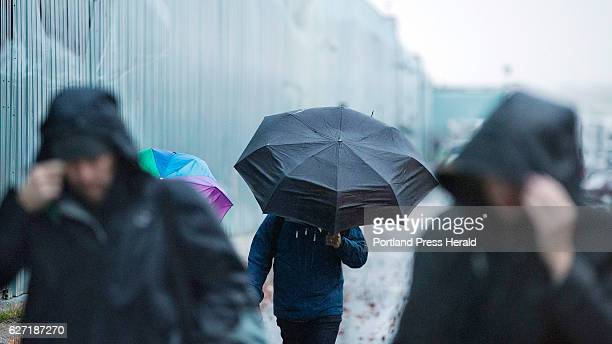 Pedestrians sheild themselves against a strong rainy headwind on Maine State Pier on Thursday morning