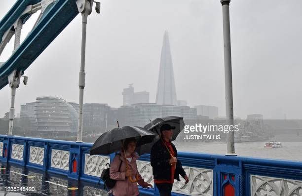Pedestrians shelter from the rain as they walk across Tower Bridge in London on September 14 following heavy rainfall.