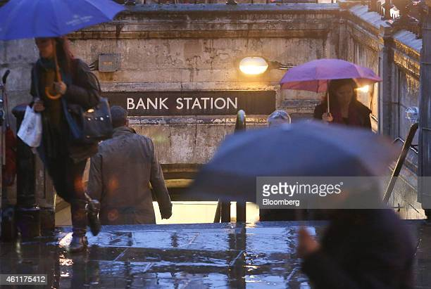 Pedestrians shelter from the rain beneath umbrellas as they exit Bank underground station near the Bank of England in London UK on Thursday Jan 8...