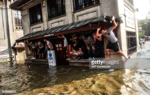 TOPSHOT Pedestrians shelter perched on a building during a heavy downpour of rain and hail at Besiktas near Istanbul on July 27 2017 / AFP PHOTO /...