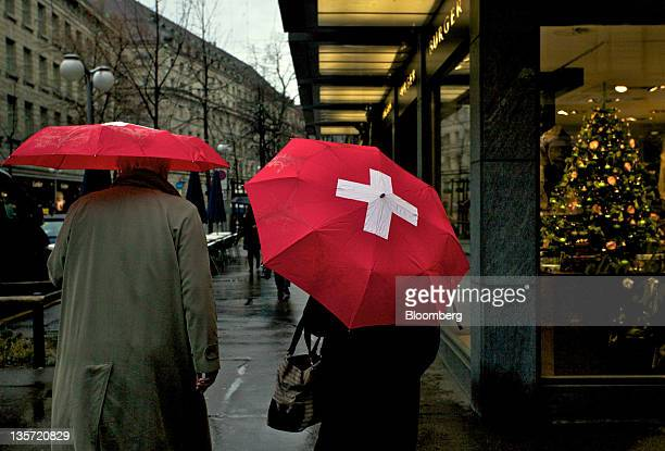 Pedestrians shelter under Swissbranded umbrellas as they walk past stores in Zurich Switzerland on Monday Dec 12 2011 Switzerland's economy is...