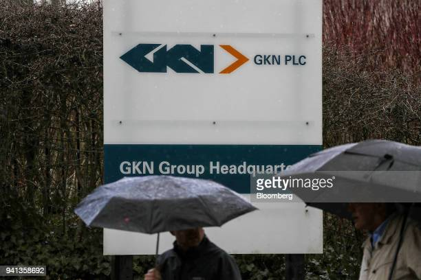 Pedestrians shelter under umbrellas as they pass a logo outside GKN Plc's company headquarters in Redditch UK on Tuesday April 3 2018 Yet another...