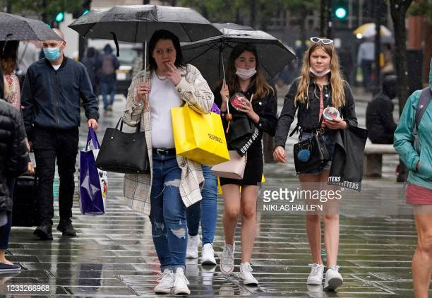 Pedestrians shelter under umbrellas as they walk down Oxford Street in the rain in London on June 4 as a day of unsettled weather interrupts a week...