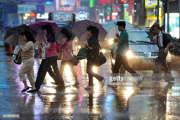 Pedestrians shield themselves from the rain with umbrellas as they cross a street in Taipei on July 22 2014 as Typhoon Matmo approaches eastern...