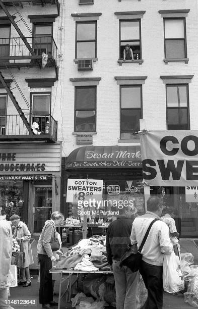 Pedestrians shop at a stall that sells 'Cotton Sweaters' on 9th Avenue in Hell's Kitchen as above them apartment building residents peer down New...