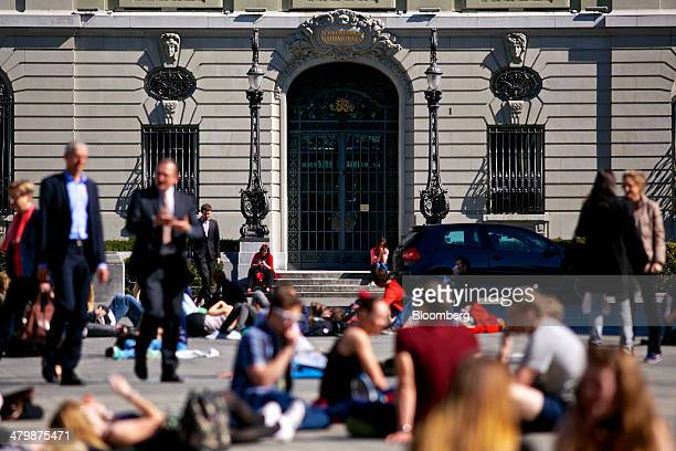 Pedestrians sits in the square outside the Swiss National Bank's headquarters in Bern Switzerland on Thursday March 20 2014 The Swiss National Bank...