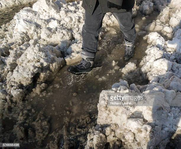 Pedestrians slog through puddles of slush and snow during their morning commute at street crossings with snow dam clogged storm drains in the Chelsea...