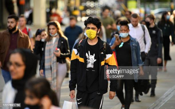 Pedestrians some wearing a face mask or covering due to the COVID19 pandemic walk in Manchester northwest England on August 3 following a rise in the...
