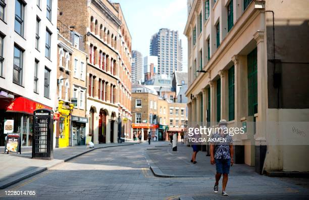 Pedestrians some wearing a face mask or covering due to the COVID19 pandemic walk along a quite shopping street in London on August 12 2020 Britain's...