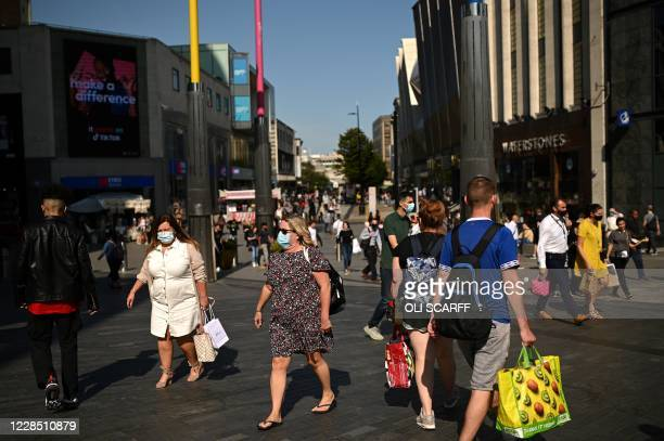 Pedestrians, some wearing a face mask or covering due to the COVID-19 pandemic, walk along a busy shopping street in Birmingham, central England on...