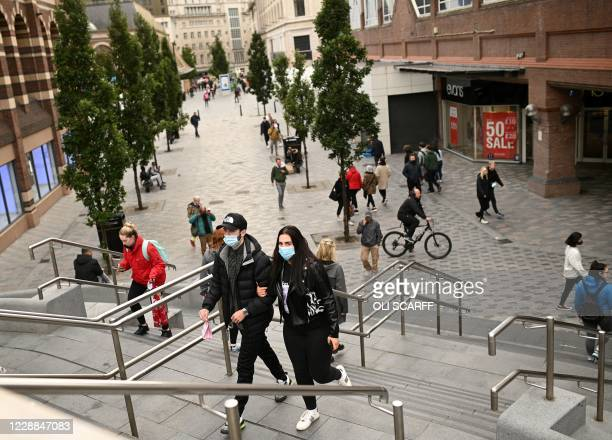Pedestrians, some wearing a face mask or covering due to the COVID-19 pandemic, walk in Liverpool, north west England on October 2 following the...