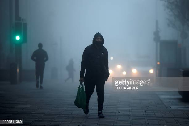 Pedestrians, some wearing a face mask or covering due to the COVID-19 pandemic, walk in the early morning fog in Walthamstow, east London on November...