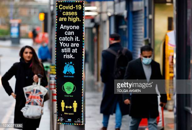 Pedestrians, some wearing a face mask or covering due to the COVID-19 pandemic, walks past Coronavirus information signs in Walthamstow in north east...