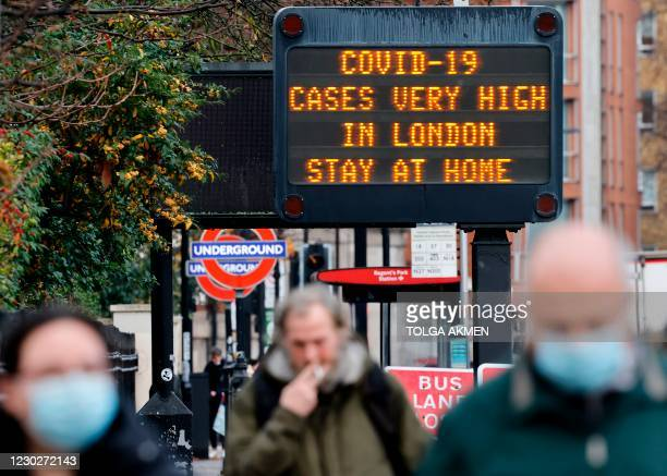 """Pedestrians, some wearing a face mask or covering due to the COVID-19 pandemic, walks past a sign alerting people that """"COVID-19 cases are very high..."""