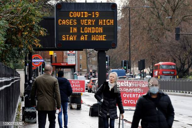 """Pedestrians, some wearing a face mask or covering due to the COVID-19 pandemic, walk past a sign alerting people that """"COVID-19 cases are very high..."""