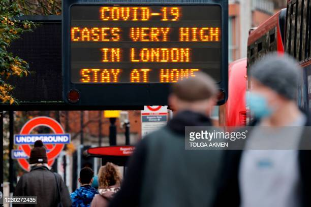 "Pedestrians, some wearing a face mask or covering due to the COVID-19 pandemic, walks past a sign alerting people that ""COVID-19 cases are very high..."