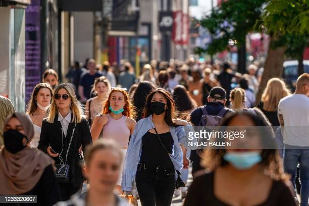 Pedestrians, some wearing face coverings due to Covid-19, walk past shops on Oxford Street in central London on June 7, 2021. - The Delta variant of...