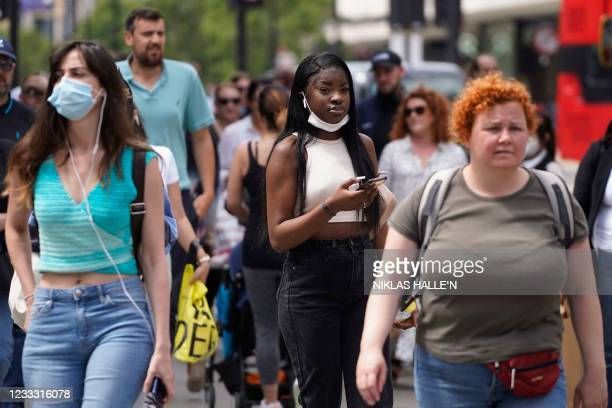 Pedestrians, some wearing face coverings walk along Oxford Street in central London on June 7, 2021. - The Delta variant of the coronavirus, first...