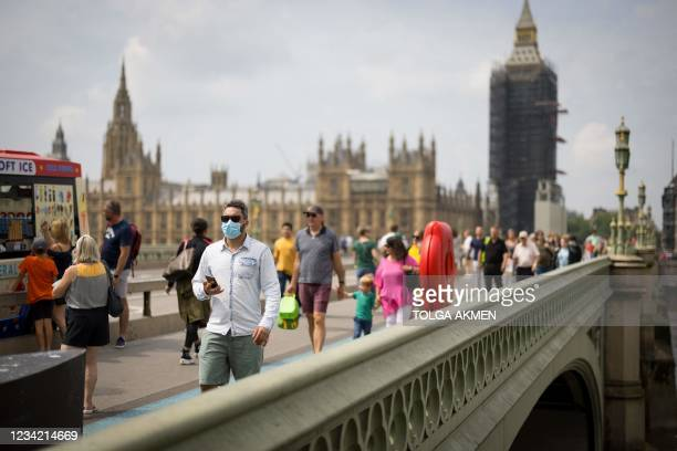 Pedestrians, some wearing face masks cross Westminster Bridge with Elizabeth Tower, better known by the nickname for the Great Bell in the clock Big...
