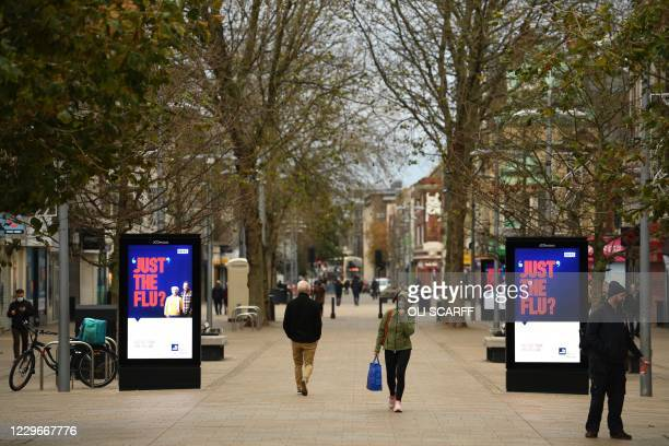 Pedestrians, some wearing face masks or coverings due to the COVID-19 pandemic, walk past COVID-19 signs in Hull, in northern England on November 18...