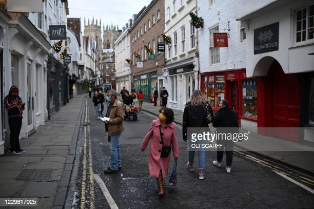 Pedestrians, some wearing face masks or coverings due to the COVID-19 pandemic, walks mast shops in York, northern England on November 27 as life...