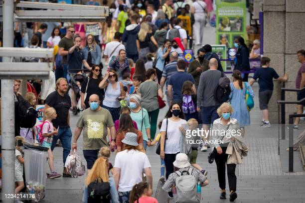 Pedestrians, some wearing face masks, walk along a street in central London on July 26, 2021. - For the first time in the latest wave of coronavirus...