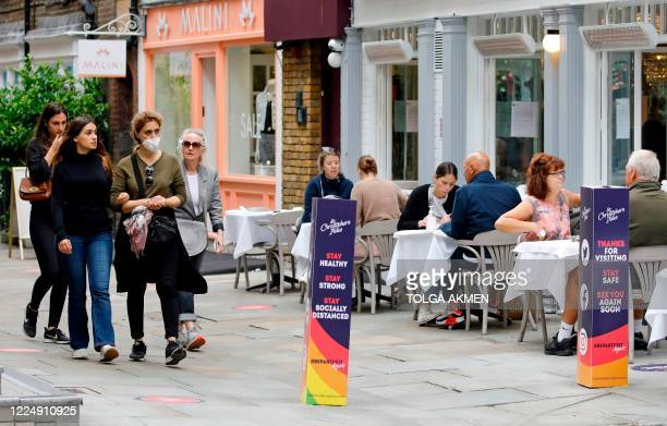 Pedestrians some wearing PPE of a face mask or covering as a precautionary measure against spreading COVID19 walk past customers sat outside a...