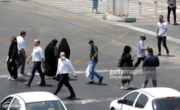 Pedestrians, some wearing protective masks due to the COVID-19 coronavirus, cross a street in the Iranian capital Tehran on June 28, 2020. - Iran's...