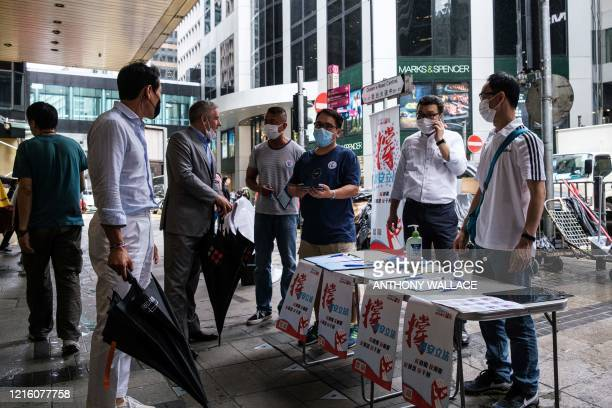 Pedestrians speak to people at a booth where people can give their signatures in support of a new security law in Hong Kong on May 29 2020 China...