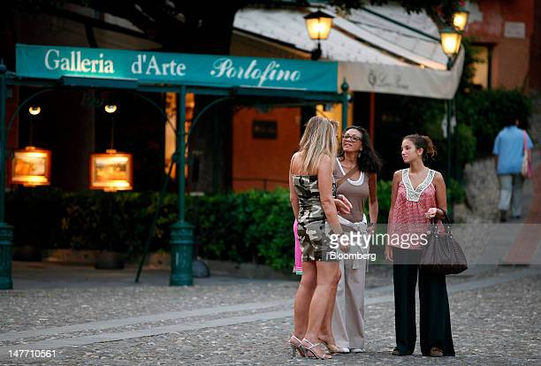 Pedestrians stand and talk outside an art gallery in Portofino Italy on Saturday June 30 2012 Italy's economy will shrink 24 percent this year twice...