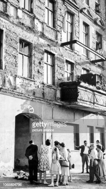 Pedestrians stand around a wreath for the dead Ida Siekmann which was placed where she had died in Berlin Wedding on 29 August 1961 Not long before...