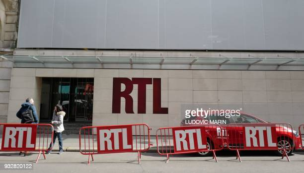 Pedestrians stand at the entrance to French radio station RTL radio's historical headquarters at Bayard Street in central Paris on March 16 ahead of...