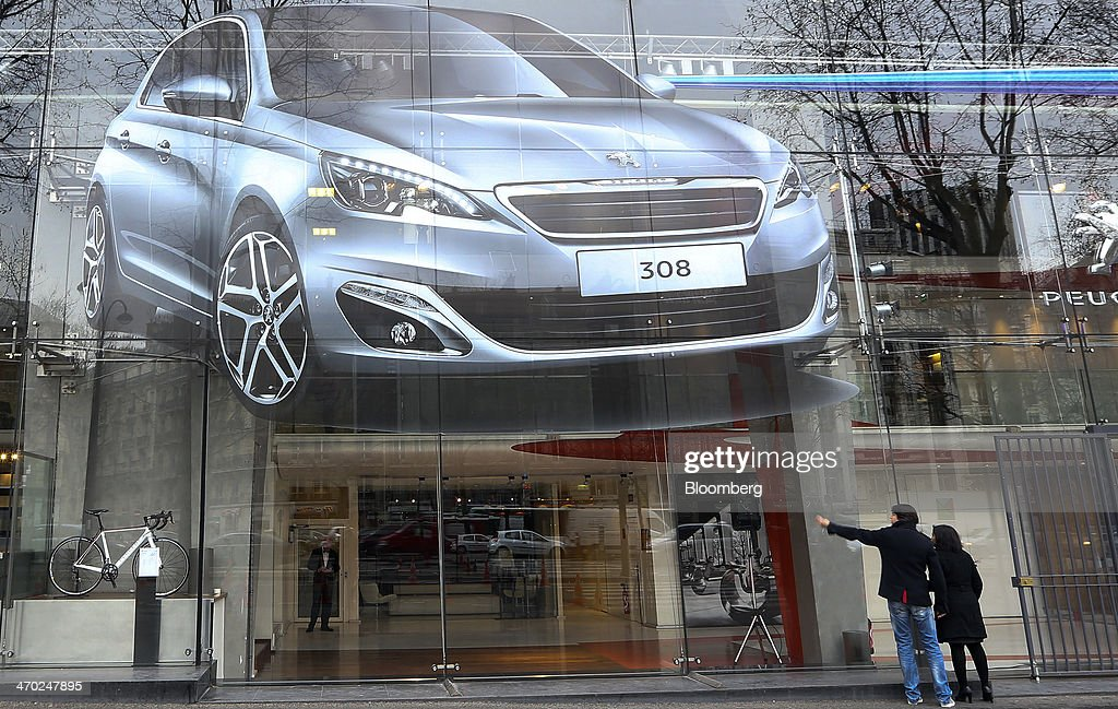 Pedestrians stand beneath a giant poster of a Peugeot 308 automobile outside a car showroom at the company's headquarters in Paris, France, on Wednesday, Feb. 19, 2014. PSA Peugeot Citroen, which hasn't posted a profit since 2011, agreed to bring in Chinese partner Dongfeng Motor Corp. and France as investors as part of a 5.27 billion-euro ($7.26 billion) rescue plan to fund new vehicles. Chris Ratcliffe/Bloomberg via Getty Images