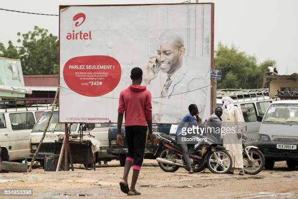 Pedestrians stand beside an advertisement for Bharti Airtel Ltd in N'Djamena Chad on Tuesday Aug 15 2017 African Development Bank and nations signed...