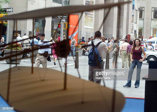 Pedestrians stand in front of a model of the 1903 Wright Flyer on display at the Centennial of Flight exhibit at Rockefeller Center August 7 2003 in...