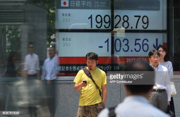 Pedestrians stand in front of a stock quotation board flashing the Nikkei 225 key index of the Tokyo Stock Exchange in front of a securities company...