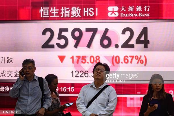 Pedestrians stand in front of a stocks display board showing the Hang Seng index at 2597624 down 067 percent in Hong Kong on August 6 2019 Hong Kong...